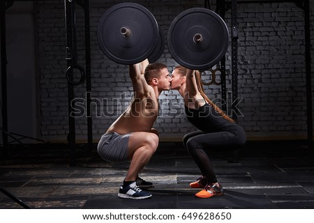 Young beautiful sportive woman and man kissing and lifting a dumbbell from squats against brick wall in the gym. #649628650