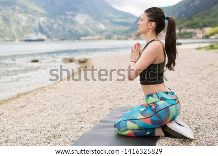Young beautiful sportive woman doing yoga on mat, exercising on the beach. Girl meditate by the coast, enjoying the relaxation. Achieving the perfect balance
