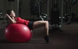 Young, beautiful, sports girl does exercises on a fitball at the gym