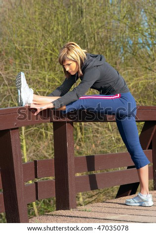 Young beautiful sportswoman stretching outdoors in a park.
