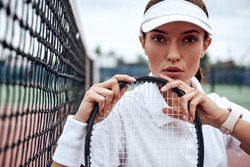 Young beautiful sportswoman with tennis racket sitting at tennis net on tennis court. Sports Fashion