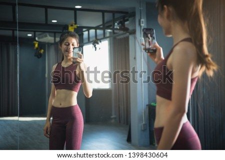 Young beautiful sporty woman taking a selfie with mobile phone for social networks at gym.  Beautiful sporty woman workout in gym healthy lifestyle.