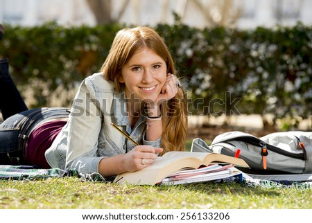 young beautiful student girl lying on campus park grass with books on rug studying happy preparing exam in university and college education concept