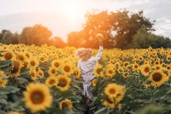 Young beautiful stylish blonde mother in a country dress and hat walks in the field of sunflowers, having fun, laughing