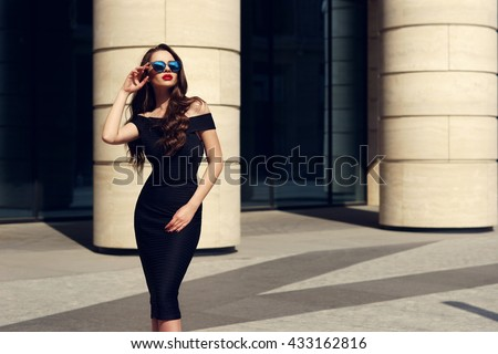 Stock Photo Young beautiful stylish girl posing at summer city streets on a sunny day. Stunning woman wearing black dress and sunglasses. Pretty model with long curly hair and red lips