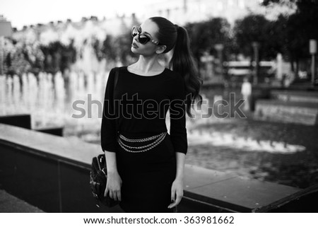 Young beautiful stylish girl walking and posing in short black dress in city near fountains. Outdoor summer portrait of young classy woman #363981662