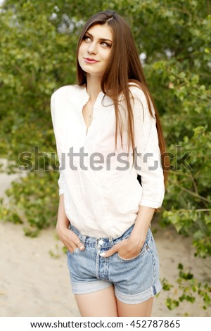 Young beautiful stylish girl with long healthy hair in white blouse and jeans shorts walking and posing in the park. Outdoors, lifestyle #452787865