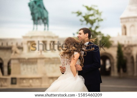 Young beautiful stylish pair of newlyweds walking by the Fisherman's Bastion in Budapest, Hungary