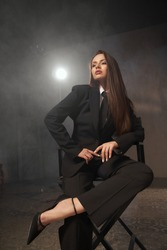 Young beautiful stylish woman in black male style suit with white blouse and tie sitting at high chair in dark interior with smoke and backlight