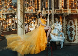 Young beautiful stylish woman sits astride a toy horse, rides a carousel. Long bright yellow dress fluttering in motion