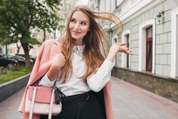 young beautiful stylish woman walking in pink coat, holding purse in hands, smiling, happy, street style, spring summer trend, black skirt, white shirt, flirty