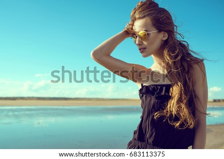 Young beautiful stylish woman with the wind in her hair wearing black open shoulder romper and trendy round mirrored sunglasses standing at the pool looking aside. Copy-space. Outdoor shot #683113375