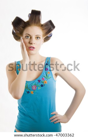Young beautiful surprised woman in blue shirt with curlers on her hair . isolated on white background. copy-space