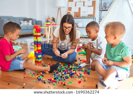 Young beautiful teacher and toddlers playing with building blocks around lots of toys at kindergarten ストックフォト ©