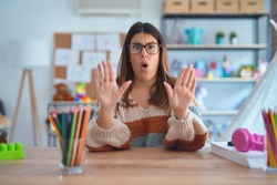 Young beautiful teacher woman wearing sweater and glasses sitting on desk at kindergarten Moving away hands palms showing refusal and denial with afraid and disgusting expression. Stop and forbidden.