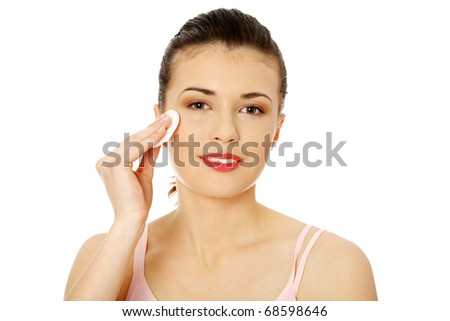 Young beautiful teen caucasian woman using a cotton pad to remove her make-up. Isolated on white