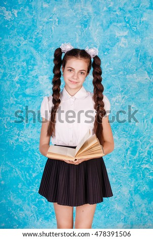 584665ac25 Young beautiful teen girl, teenager, school girl, standing on a background  of blue