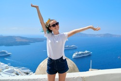 Young beautiful teenager girl tourist posing smiling, background summer sunny scenic sea landscape with white cruise liners in Aegean Sea on famous Greek island Santorini