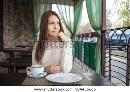 Young beautiful thoughtful brunette woman waiting in cafe terrace with a cappuccino cup