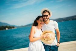 Young beautiful tourist couple enjoying summer holiday on the seaside