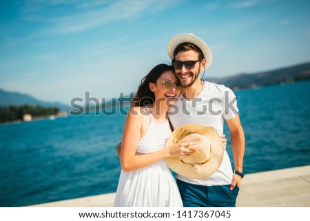 Young beautiful tourist couple enjoying summer holiday on the seaside