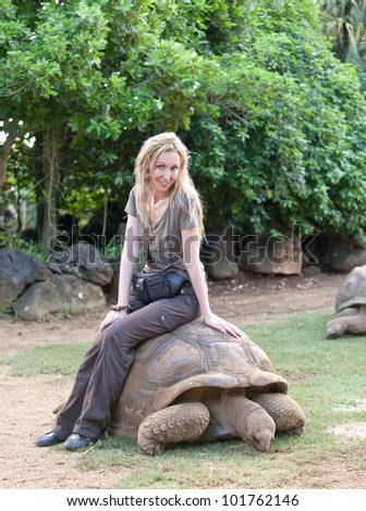young beautiful tourist woman riding  on giant turtle in La Vanille Reserve park
