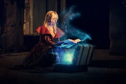 Young beautiful witch in a dark room reads a magical book and conjurer