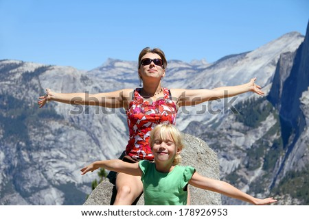 Young beautiful woman and her little daughter enjoying the sunlight sitting on the rock