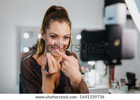 Young beautiful woman and professional beauty make up artist vlogger or blogger recording makeup tutorial to share on website or social media. Stockfoto ©