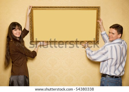 young beautiful woman and smiling man hang up on wall picture in frame