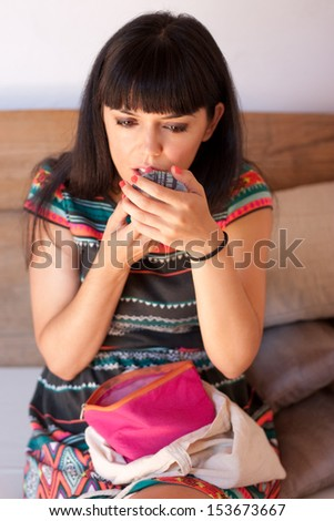Young beautiful woman applying lipstick under natural light