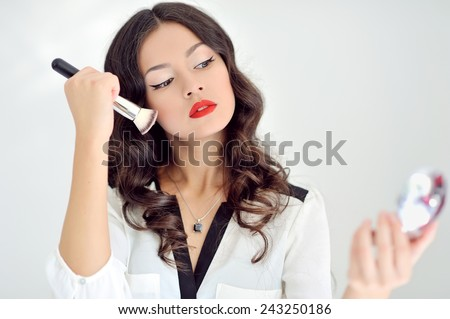 Young beautiful woman applying make-up