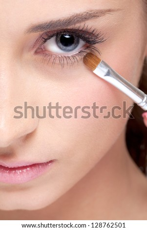 Young beautiful woman applying makeup eye shadows by brush