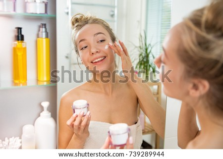 Young beautiful woman applying moisturising cream on skin in bathroom. Standing in towel with little jar of moisturizer, looking in the mirror, laughing and having fun.  Morning skincare routine.   #739289944