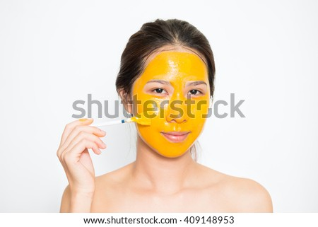 Young beautiful woman applying yogurt and turmeric facial mask Skin care, beauty treatments on white background #409148953