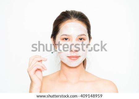 Young beautiful woman applying yogurt facial mask Skin care, beauty treatments on white background #409148959