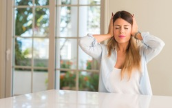 Young beautiful woman at home covering ears ignoring annoying loud noise, plugs ears to avoid hearing sound. Noisy music is a problem.