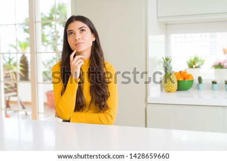Young beautiful woman at home on white table with hand on chin thinking about question, pensive expression. Smiling with thoughtful face. Doubt concept.