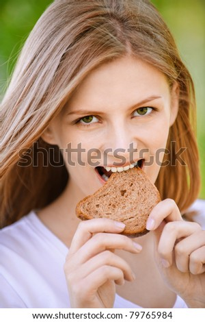 Young beautiful woman bites piece of stale bread, on green background of summer city park.