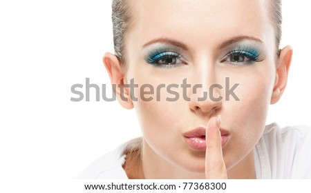 Young beautiful woman calls for silence, lifting forefinger to lips, on white background.