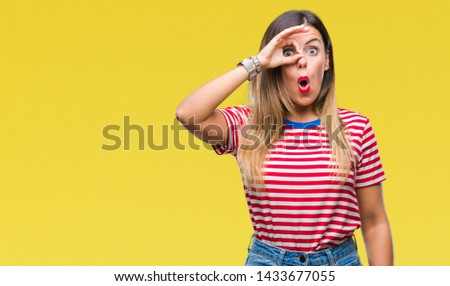 Young beautiful woman casual look over isolated background doing ok gesture shocked with surprised face, eye looking through fingers. Unbelieving expression. #1433677055