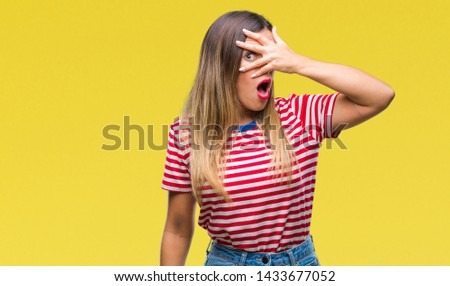 Young beautiful woman casual look over isolated background peeking in shock covering face and eyes with hand, looking through fingers with embarrassed expression. #1433677052