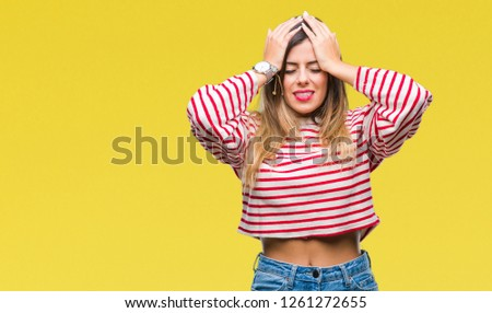 Young beautiful woman casual stripes winter sweater over isolated background suffering from headache desperate and stressed because pain and migraine. Hands on head. #1261272655