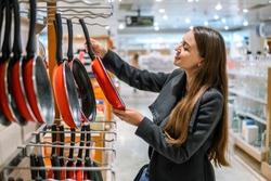 young beautiful woman choosing frying pan utensil dishes in a store supermarket shop.
