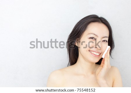 Young beautiful woman cleaning her face with cotton