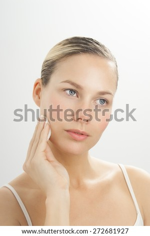 Young beautiful woman cleansing face with toner on cotton disk. Makeup removal in skincare routine.