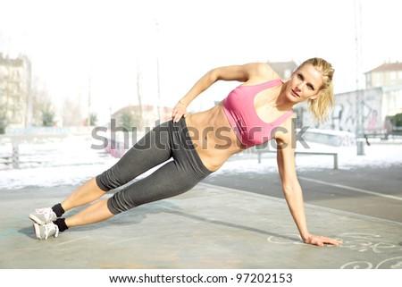 Young beautiful woman doing core workout outside