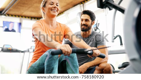 Photo of  Young beautiful woman doing exercises with personal trainer