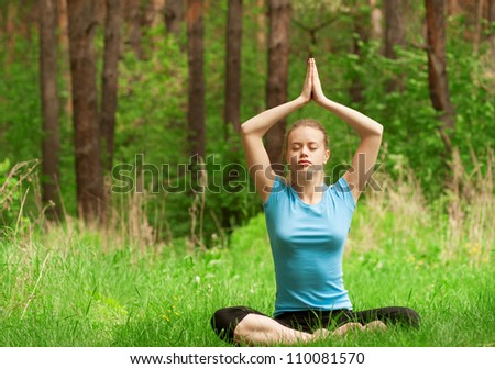 Young beautiful woman doing yoga meditation exercise in forest outdoors