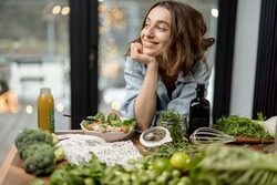 Young beautiful woman dreaming near healthy diet salad and green smoothie in the kitchen. Wellness and health care concept. High quality photo